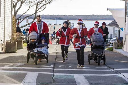 Mattapoisett, Massachusetts, USA - December 7, 2019: Strollers on the move at start of Mattapoisett Santa 5K Run. Editorial use only.