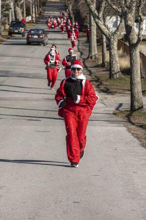 Mattapoisett, Massachusetts, USA - December 7, 2019: Running Santas heading for finish line of Mattapoisett Santa 5K Run. Editorial use only.