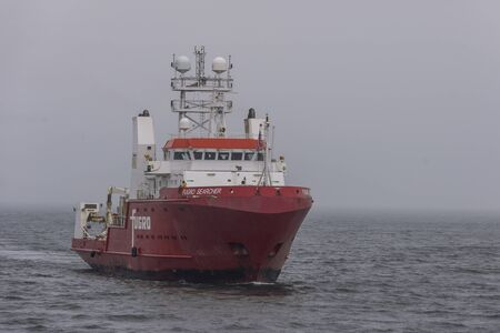New Bedford, Massachusetts, USA - December 7, 2019: Survey vessel Fugro Searcher coming out of Buzzards Bay on rainy morning