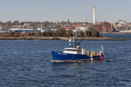 Fairhaven, Massachusetts, USA - December 7, 2019: Lobster boat Miss Emma leaving port with New Bedford in background