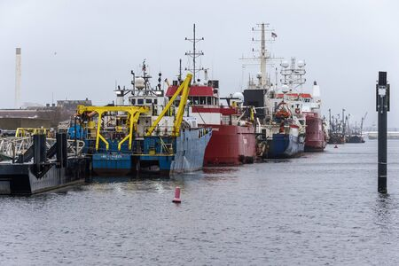 New Bedford, Massachusetts, USA - December 10, 2019: Lineup of offshore survey vessels along Marine Commerce Terminal dock on foggy morning Redakční