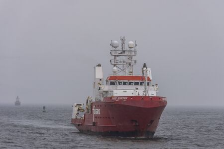 New Bedford, Massachusetts, USA - December 9, 2019: Offshore survey vessel Fugro Searcher coming out of foggy Buzzards Bay after working on Long Island Sound Redakční