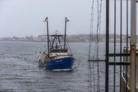 New Bedford, Massachusetts, USA - December 9, 2019: Lobster boat Debbie Ann, hailing port Point Judith, Rhode Island, approaching hurricane barrier on rainy morning