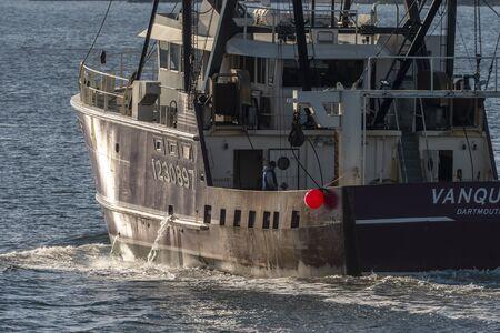 Fairhaven, Massachusetts, USA - December 7, 2019: Commercial fishing vessel Vanquish, hailing port Dartmouth, Massachusetts, heading to sea on sunny morning