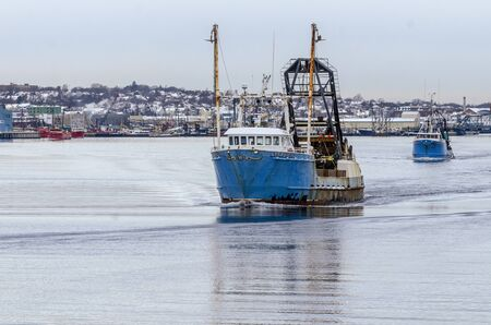 New Bedford, Massachusetts, USA - December 4, 2019: Clammers Starlight and Timberline I cross New Bedford inner harbor on their way fishing