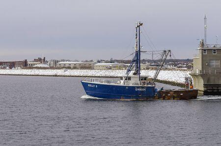 Fairhaven, Massachusetts, USA - December 4, 2019: Commercial fishing vessel Kelly S transiting hurricane barrier as she leaves port