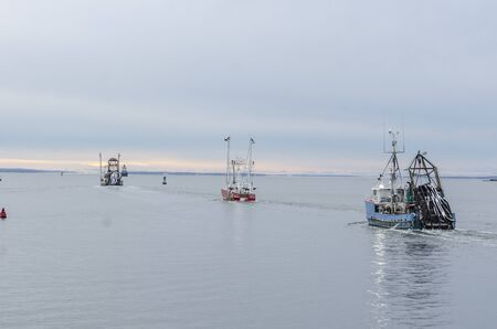 New Bedford, Massachusetts, USA - December 4, 2019: String of commercial fishing boats crossing New Bedford outer harbor to go fishing
