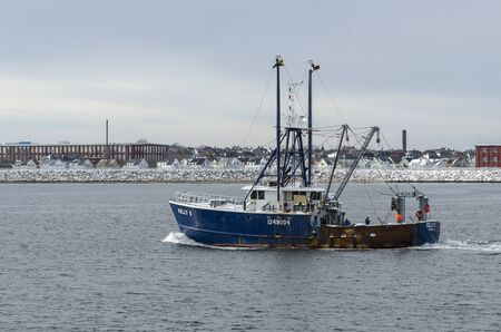 Fairhaven, Massachusetts, USA - December 4, 2019: Commercial fishing vessel Kelly S passing factories and residential area in New Bedford as she leaves Fairhaven