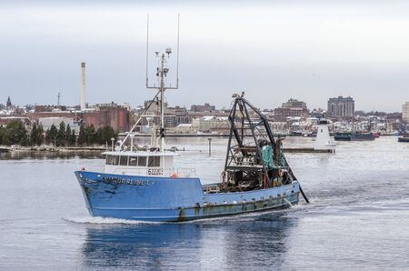 New Bedford, Massachusetts, USA - December 4, 2019: Commercial fishing boat Timberline I, hailing port Atlantic City, New Jersey, passing lighthouse on her way out of New Bedford