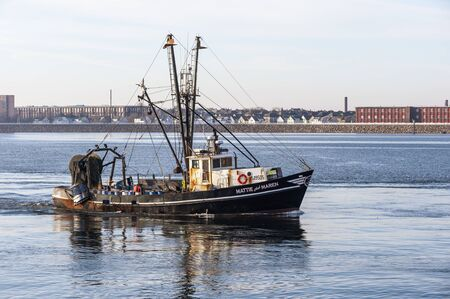 New Bedford, Massachusetts, USA - November 26, 2019: Commercial fishing boat Mattie and Maren, hailing port Point Judith, Rhode Island, crossing New Bedford outer harbor with residential neighborhood and factories in background Redakční