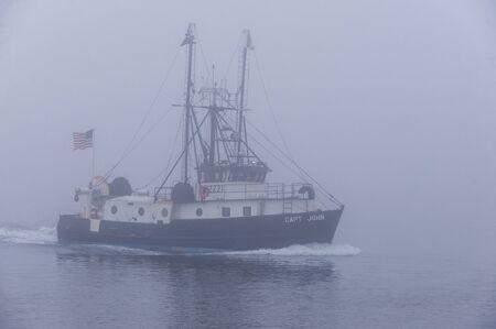 New Bedford, Massachusetts, USA - November 27, 2019: Commercial fishing boat Capt. John returning to port in heavy fog