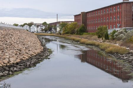 Low tide along tidal channel running inside New Bedford hurricane barrier