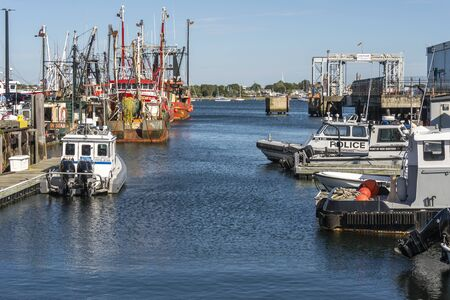 New Bedford, Massachusetts, USA – September 28, 2019: Patrol boats and fishing boats share channel between Pier 3 and State Pier along New Bedford waterfront Redakční