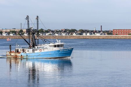 New Bedford, Massachusetts, USA - August 27, 2019: Commercial fishing boat Miss Taylor, hailing port Atlantic City, New Jersey, passing New Bedford factories and homes