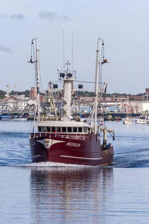 New Bedford, Massachusetts, USA - August 27, 2019: Commercial fishing boat Regulus, hailing port Stonington, Connecticut, crossing New Bedford inner harbor