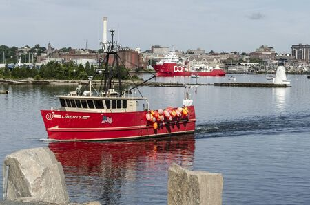 New Bedford, Massachusetts, USA - August 27, 2019: Commercial fishing boat Liberty and survey vessel DOF Geosea crossing New Bedford inner harbor