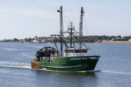 New Bedford, Massachusetts, USA - August 20, 2019: Commercial fishing boat Lightning Bay, hailing port Point Judith, Rhode Island, crossing New Bedford outer harbor
