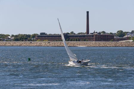 New Bedford, Massachusetts, USA - August 20, 2019: Sailboat Sea Swell cutting briskly across New Bedford outer harbor with hurricane barrier and factory in background