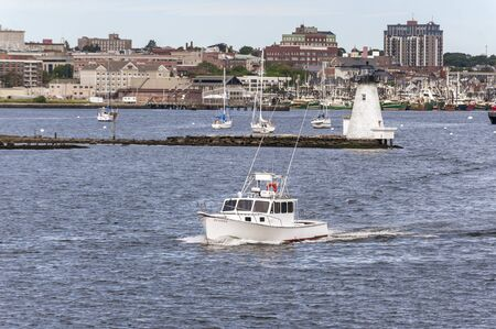 New Bedford, Massachusetts, USA - September 8, 2019: Powerboat Islander passing Palmer Island Light Station