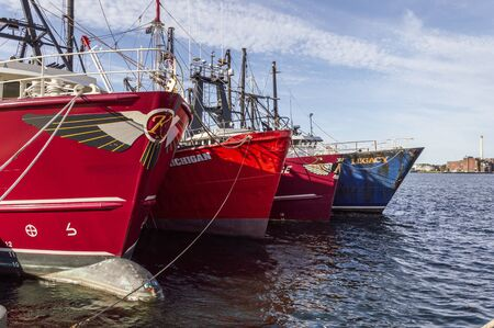 Fairhaven, Massachusetts, USA - September 8, 2019: Commercial fishing boats rafted together at Union Wharf on summer morning