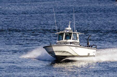 Fairhaven, Massachusetts, USA - August 5, 2019: Fairhaven Harbormaster patrol boat crossing New Bedford inner harbor
