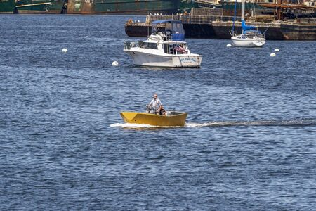 New Bedford, Massachusetts, USA - August 9, 2019: Boat driver anticipating weather conditions in Buzzards Bay as he heads out of New Bedford harbor on summer morning