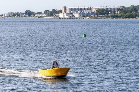 New Bedford, Massachusetts, USA - August 3, 2019: Man in brightly colored skiff moving briskly across New Bedford outer harbor on a summer morning
