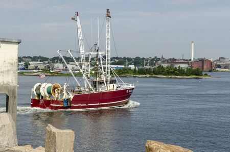 New Bedford, Massachusetts, USA – July 22, 2019: Commercial fishing boat Maizey James, hailing port Point Pleasant Beach, NJ, transiting New Bedford hurricane protection barrier