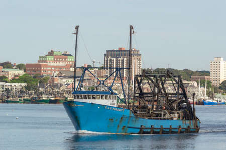New Bedford, Massachusetts, USA - September 5, 2018: Commercial fishing vessel E.S.S. Pursuit crossing Acushnet River with New Bedford waterfront in background Sajtókép