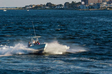 New Bedford, Massachusetts, USA - September 5, 2018: Rough ride aboard powerboat banging across wind-driven chop on Acushnet River in early evening