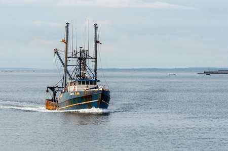 New Bedford, Massachusetts, USA - August 15, 2018: Commercial fishing vessel Capt. Bob, hailing port Cape May, NJ, coming out of foggy Buzzards Bay Editorial