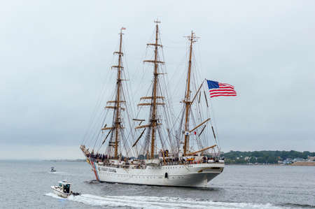 New Bedford, Massachusetts, USA - August 13, 2018: U.S. Coast Guard training cutter Eagle leaving New Bedford under cloudy skies. The 295-foot training vessel was paying a weekend visit to the city.