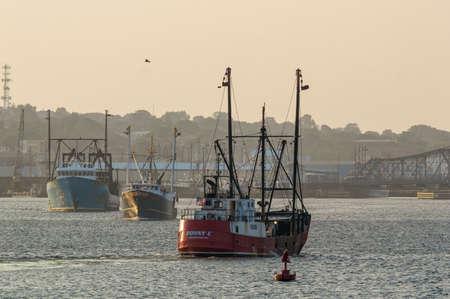 New Bedford, Massachusetts, USA - August 29, 2018: Fishing boat traffic on Acushnet River on hazy summer evening