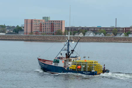 New Bedford, Massachusetts, USA - May 17, 2018: Lobster boat Miss Emma outbound and stacked with lobster pots