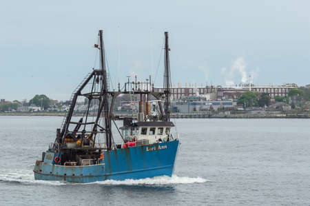 New Bedford, Massachusetts, USA - May 17, 2018: Commercial fishing vessel Lori Ann crossing New Bedford outer harbor with factory in background