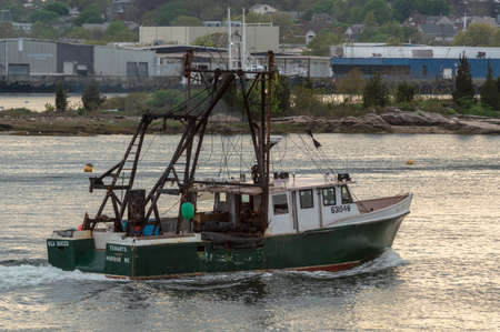 New Bedford, Massachusetts, USA - May 17, 2018: Commercial fishing vessel Sea Duced, hailing port Tenants Harbor, Maine, crossing New Bedford inner harbor at sunset