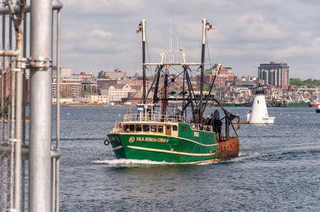 New Bedford, Massachusetts, USA - May 16, 2018: Commercial fishing boat Vila Nova Do Corvo I nearing hurricane barrier in New Bedford harbor