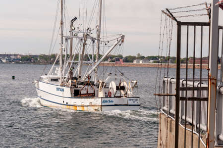 New Bedford, Massachusetts, USA - May 16, 2018: Commercial fishing boat Little Tootie, hailing port Newport News, VA, clearing hurricane barrier in New Bedford harbor