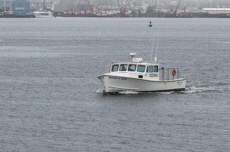 New Bedford, Massachusetts, USA - May 15, 2018: Lobster boat Sherri & Deke crossing New Bedford harbor on foggy evening
