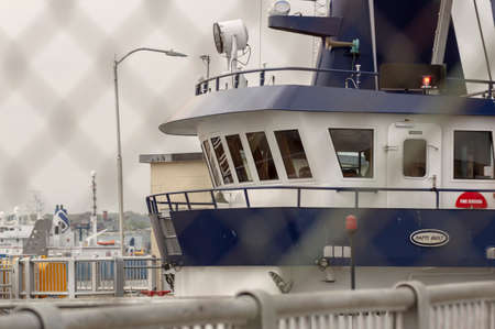 New Bedford, Massachusetts, USA - May 15, 2018: Pilothouse of fishing vessel Sea Watcher II looms as the clammer passes through the New Bedford hurricane barrier