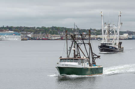New Bedford, Massachusetts, USA - May 14, 2018: Commercial fishing boats Sea Duced, hailing port Tenants Harbor, Maine, and Helen Louise, hailing port Aurora, North Carolina, crossing New Bedford inner harbor