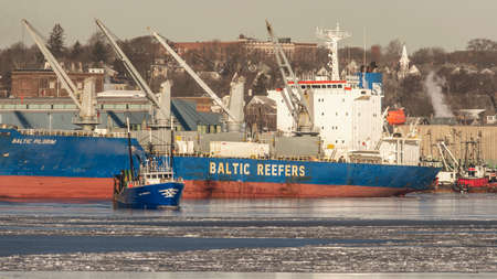 New Bedford, Massachusetts, USA - January 10, 2018: Trawler Luso American I leaving dock in icy New Bedford inner harbor with reefer Baltic Pilgrim in background