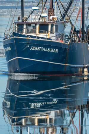 New Bedford, Massachusetts, USA - January 10, 2018: Reflection of commercial fishing boat Jessica & Susan crossing icy Acushnet River