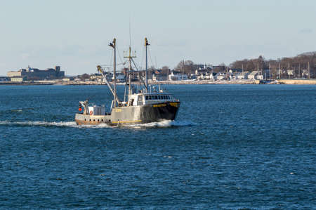 New Bedford, Massachusetts, USA - March 17, 2018: Fishing vessel Reflection in New Bedford outer harbor