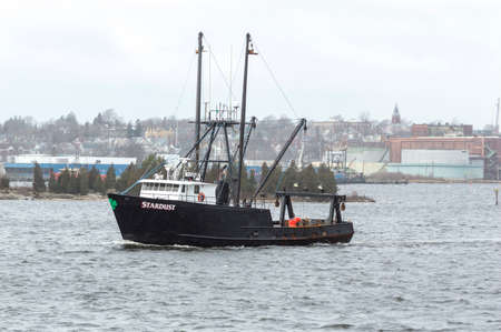 New Bedford, Massachusetts, USA - March 5, 2018: Fishing vessel Stardust leaving New Bedford on foggy late winter morning