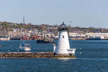 New Bedford, Massachusetts, USA - May 13, 2020: Lighthouse, sailboat and commercial fishing boat set against New Bedford waterfront