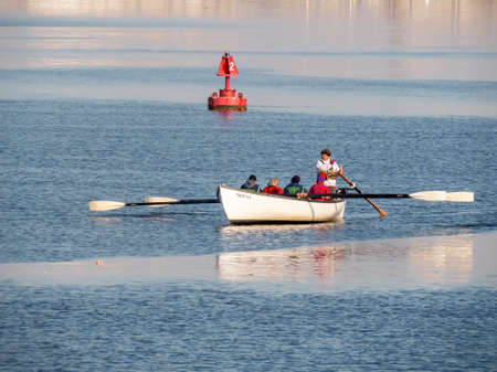 Fairhaven, Massachusetts, USA - March 1, 2018: Members of Buzzards Bay Rowing Club power whaleboat across the Acushnet River on calm day
