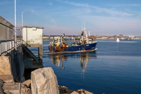 New Bedford, Massachusetts, USA - March 1, 2018: Fishing vessel Nobska passing through hurricane barrier into New Bedford inner harbor ahead of impending nor'easter