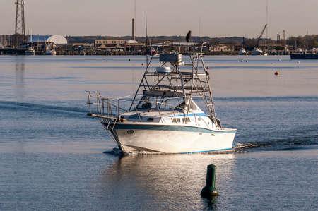 New Bedford, Massachusetts, USA - May 14, 2020: Recreational fishing boat idling toward dock along New Bedford waterfront