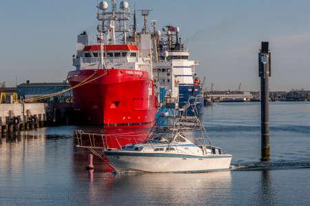 New Bedford, Massachusetts, USA - May 14, 2020: Recreational fishing boat idling toward dock near Marine Commerce Terminal Redactioneel